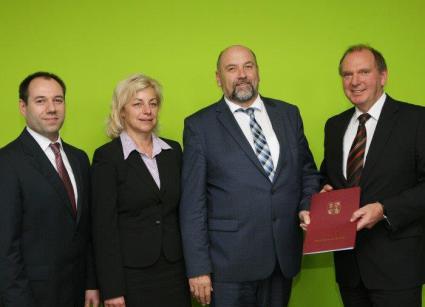 Il ministro Harry Glawe (terzo da sinistra) porge la decisione di finanziamento a Manfred Remus (destra) di Arla Foods Germany GmbH. Si congratulano anche l'amministratore del distretto Kerstin Weiss (secondo da sinistra) e il direttore di stabilimento di Upahl, Bernd Lohse (sinistra).